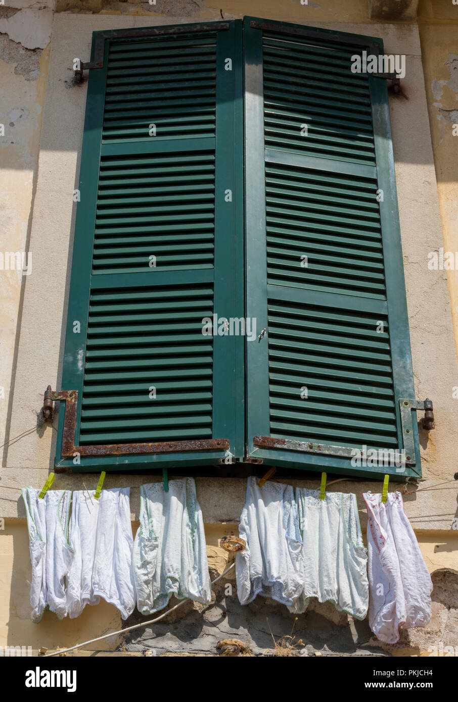 pairs of knickers and big pants hanging on a washing line below some green painted wodden shutters and a window in the old town of kerkyra on corfu. - Stock Image