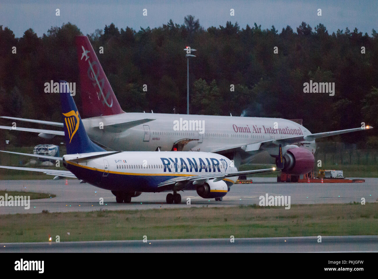 Low cost airline Ryanair aircraft Boeing 737-800 and charter Omni Air International Boeing 777-2U8(ER) in Gdansk Lech Walesa Airport in Gdansk, Poland - Stock Image