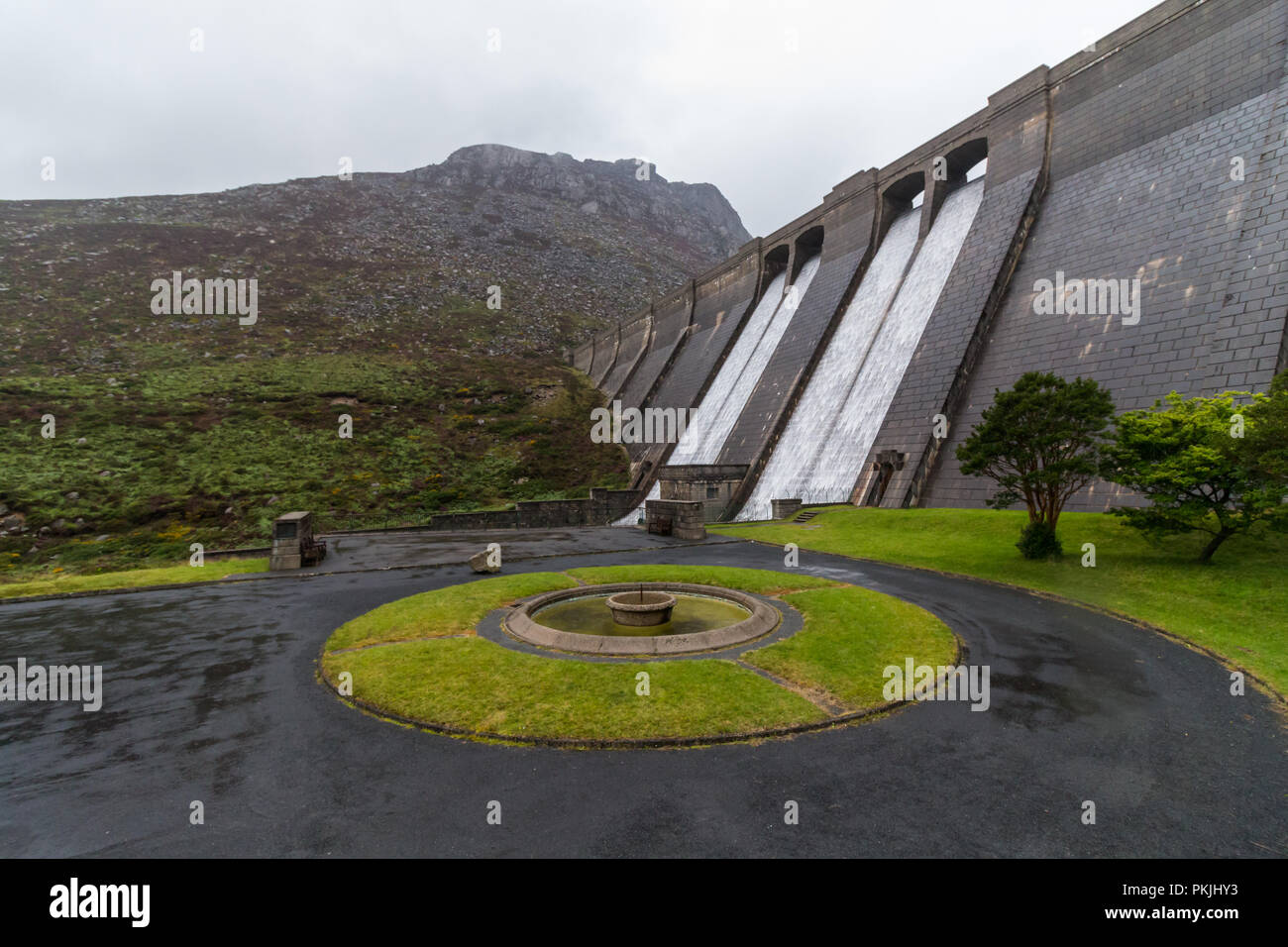 Water is cascading down the dam wall at Ben Crom Reservoir.in the heart of the Mourne Mountains. Ben Crom mountain is seen above the dam. A turning ci - Stock Image