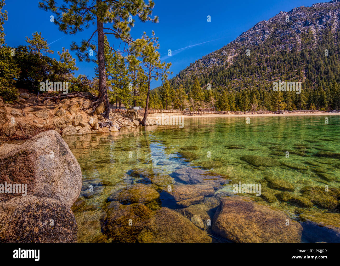 Long exposure of Sand Harbor at Lake Tahoe North, Nevada county, California, USA, featuring aqua transparent water, rocky shore  on a blue cloudless s Stock Photo
