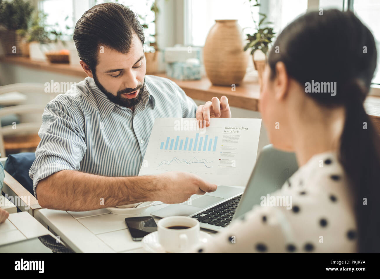 Smart bearded young man showing the diagram - Stock Image