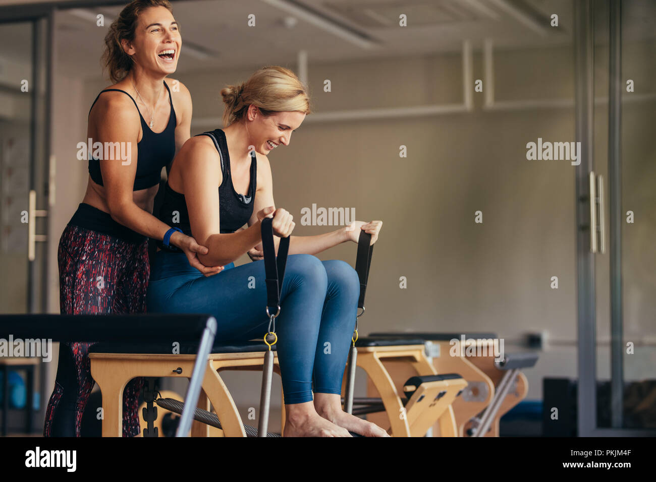 Smiling woman at the gym doing pilates training with her trainer. Trainer helping woman in pulling the stretch bands while doing pilates workout. - Stock Image