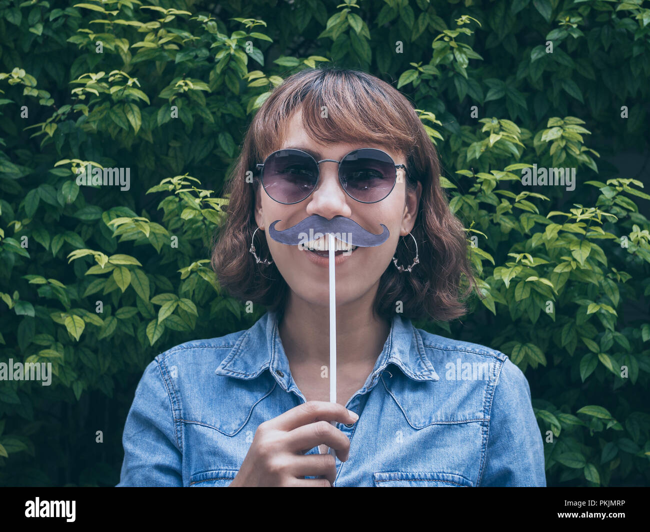 bc3bef0050 Beautiful asian woman short hair wearing blue jeans shirt and sunglasses  smiling with fake mustache on green leaves background.