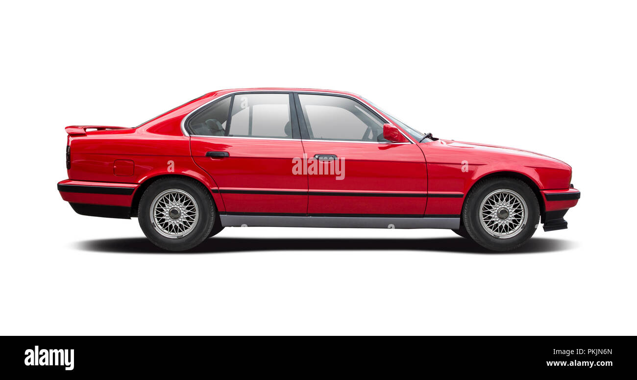 Red BMW series 5 side view on white background - Stock Image