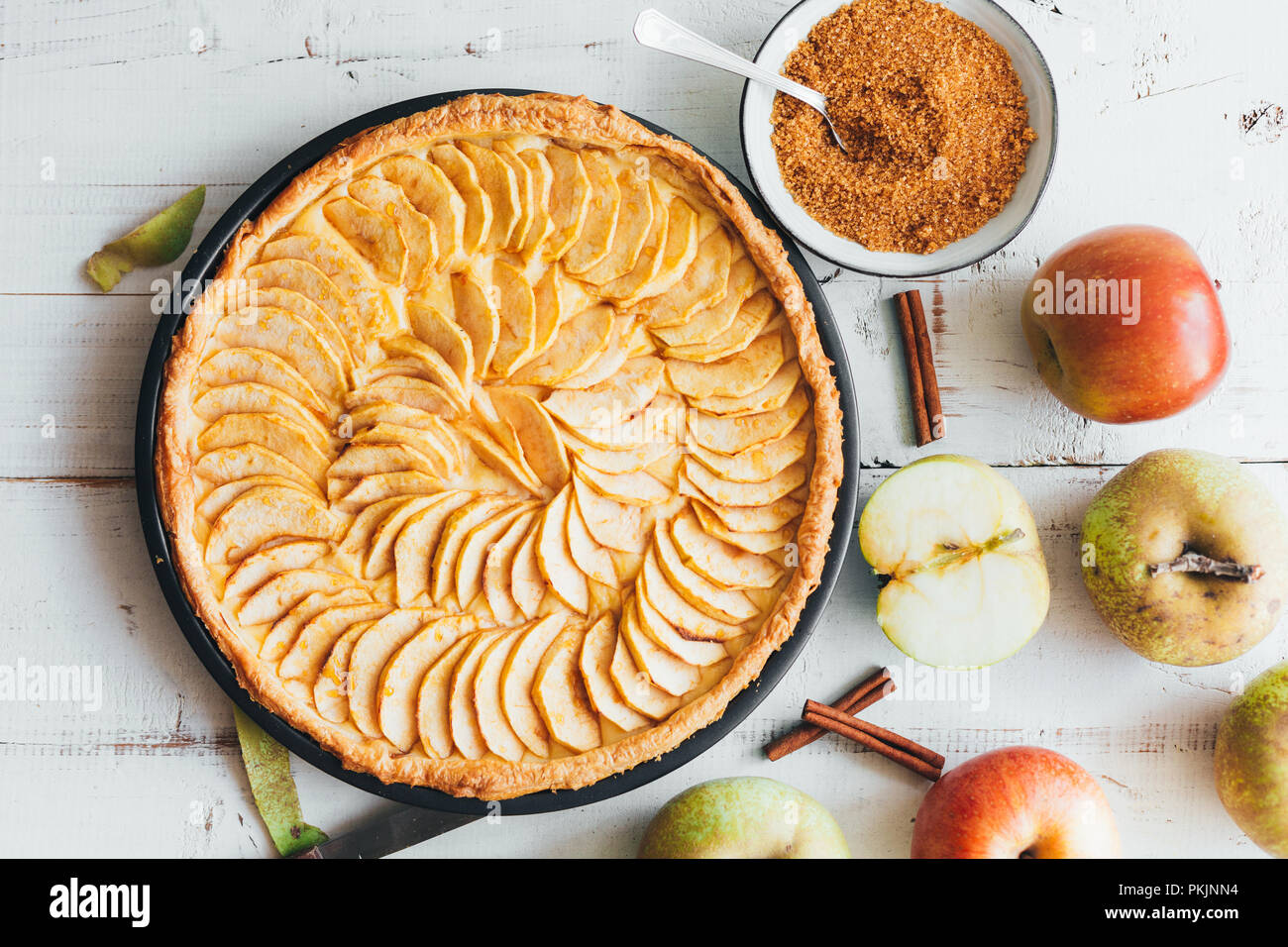 Freshly baked apple pie tart with custard filling on a rustic white wooden background. Top view - Stock Image