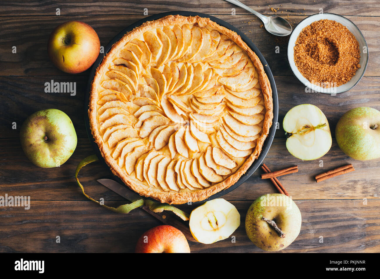 Freshly baked apple pie tart with custard filling on a rustic wooden table. Top view - Stock Image