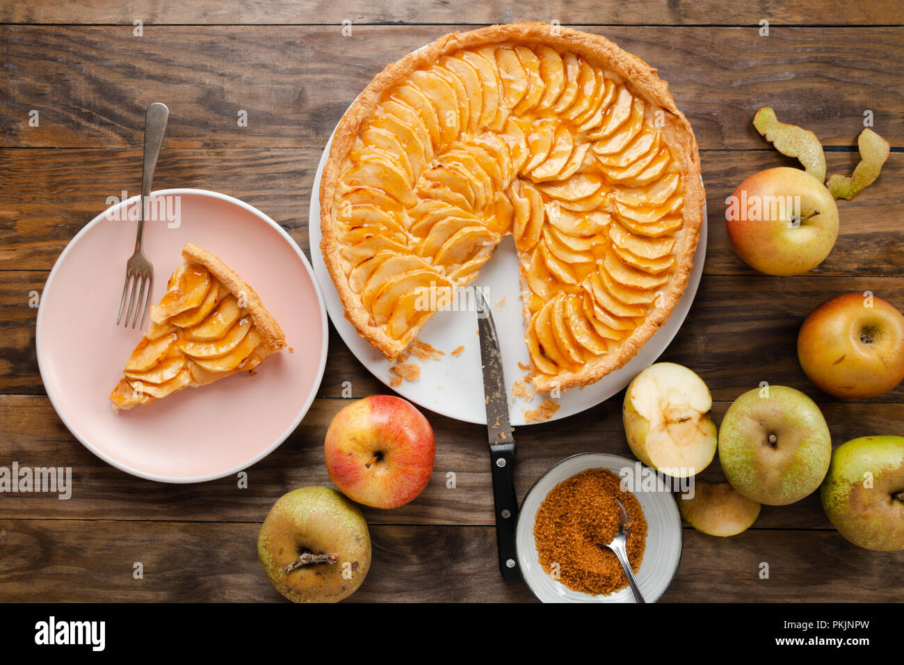 Traditional apple pie tart with custard filling and jam cover on a rustic wooden table. Top view - Stock Image