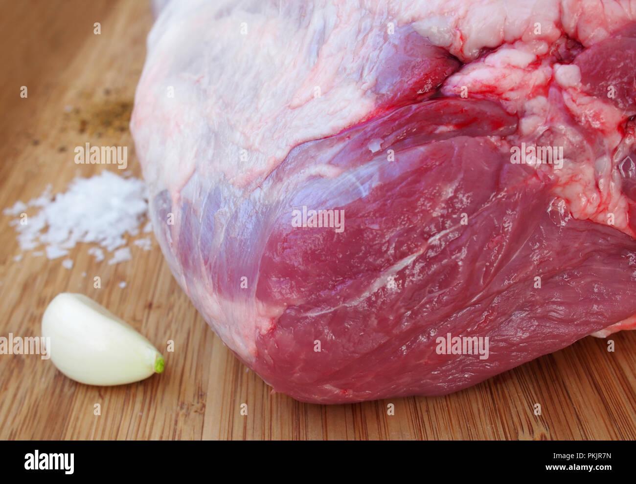 Fresh and raw meat. Leg of lamb on wood background - Stock Image