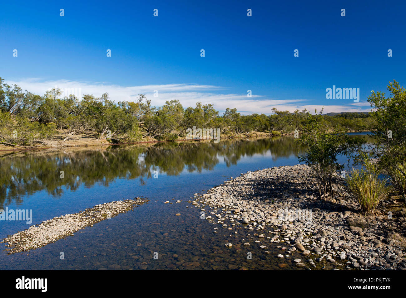 Calm blue waters of Clarence River slicing through forested landscape under blue sky in northern NSW Australia - Stock Image