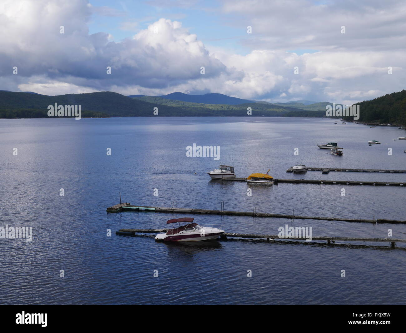 Boats docked on a lake in the Adirondack mountains of New York state - Stock Image