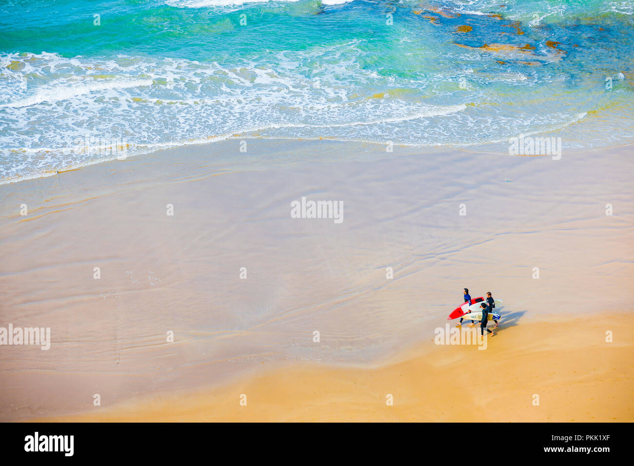 Bird's-eye overhead view of three surfers walking along sandy beach - Stock Image
