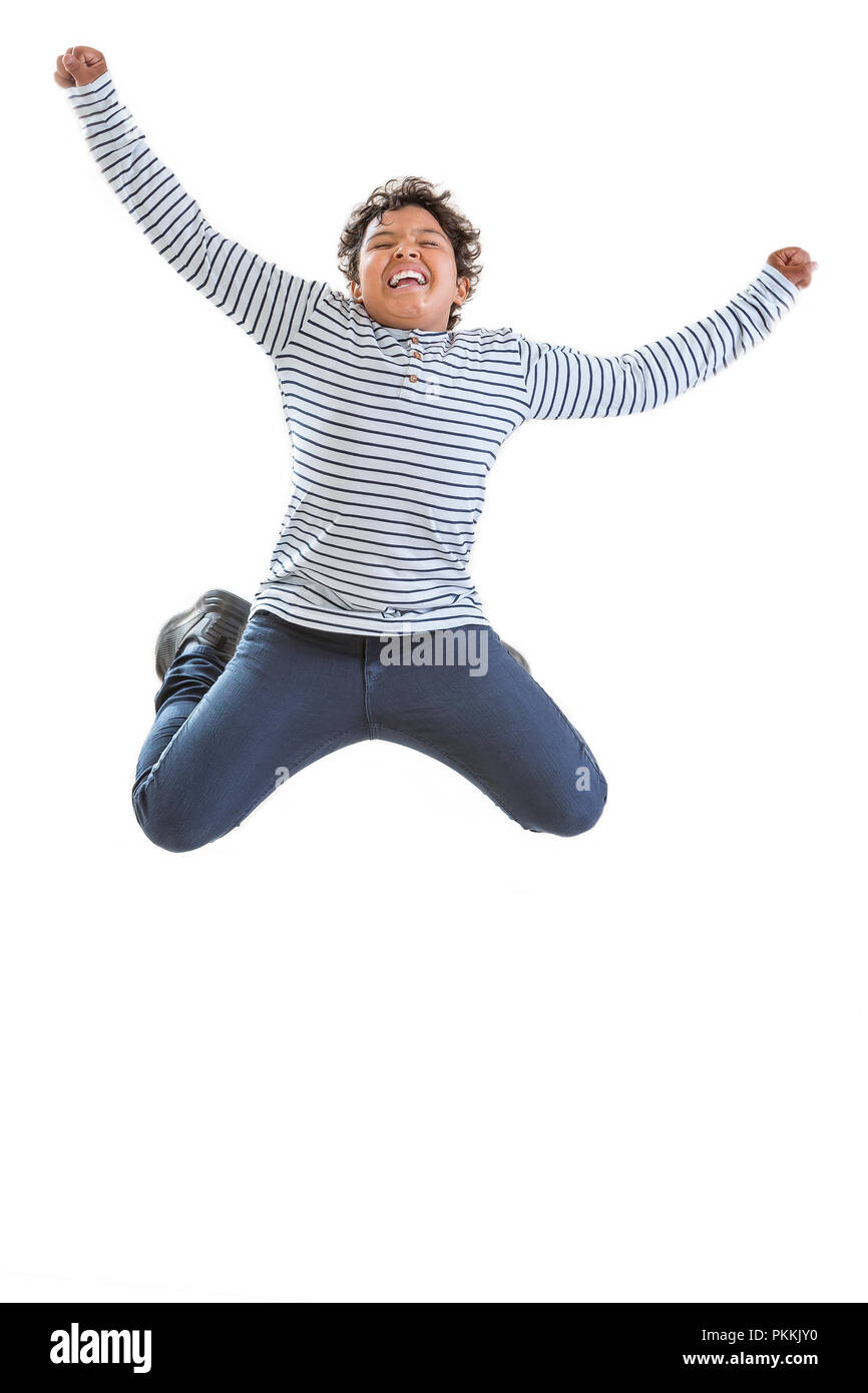 jomping boy. Cheerful young teenager boy jumping for joy. Isolated over white. - Stock Image