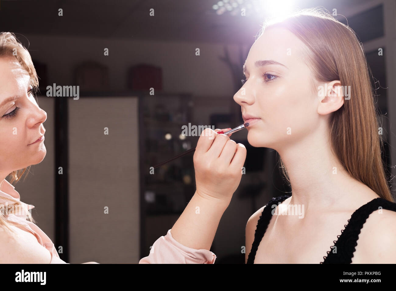 makeup artist applying a lip gloss on lips of a young pretty client. concept of professional make up couching - Stock Image