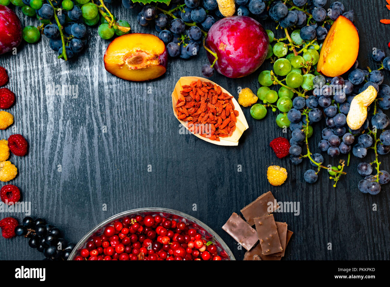food for your health. Brain boosting health food background border with nuts, fruit, chocolate, goji, raspberrys, grapes. Food high for vitamins, mine - Stock Image