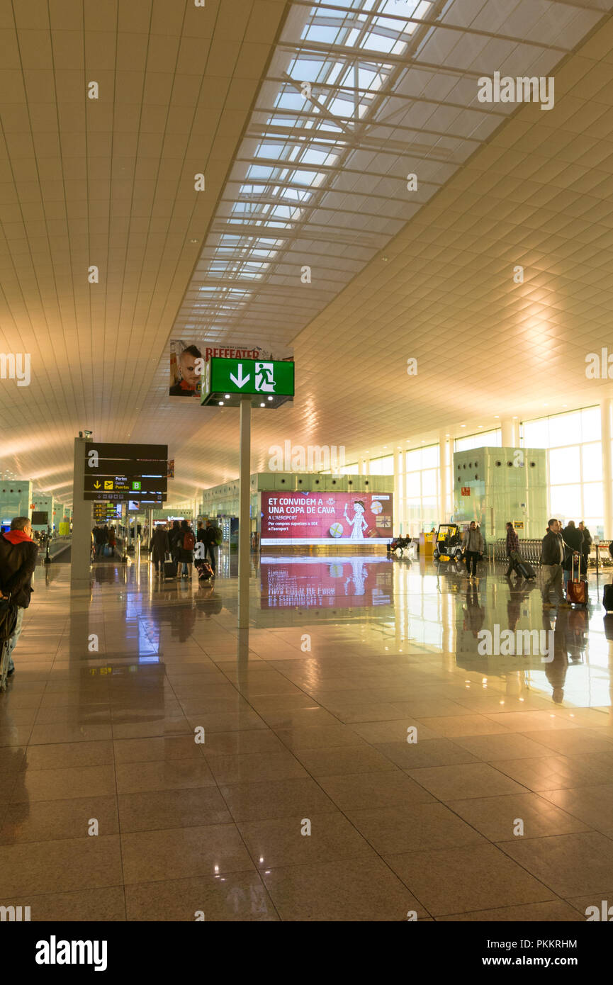 BARCELONA, SPAIN - DECEMBER 29, 2017: Passengers with luggage in Barcelona International Airport El Prat interior . Airport is one of the biggest in E - Stock Image