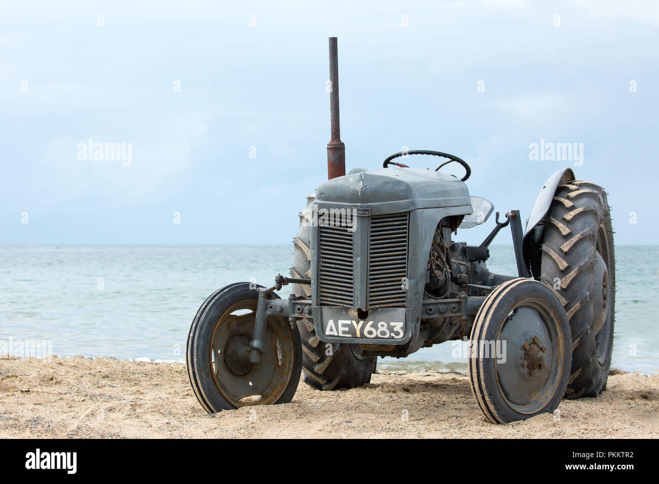 Landscape shot of a grey, vintage tractor on a UK beach waiting for its next towing job. Out of retirement  for the summer season. UK leisure pursuits - Stock Image