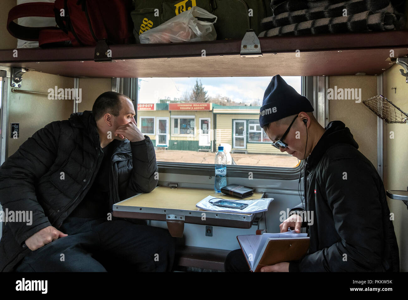 SIBERIA, RUSSIA - MARCH 20, 2018: The Russian passenger is watching outside from train. Khabarovsk, Russia. - Stock Image