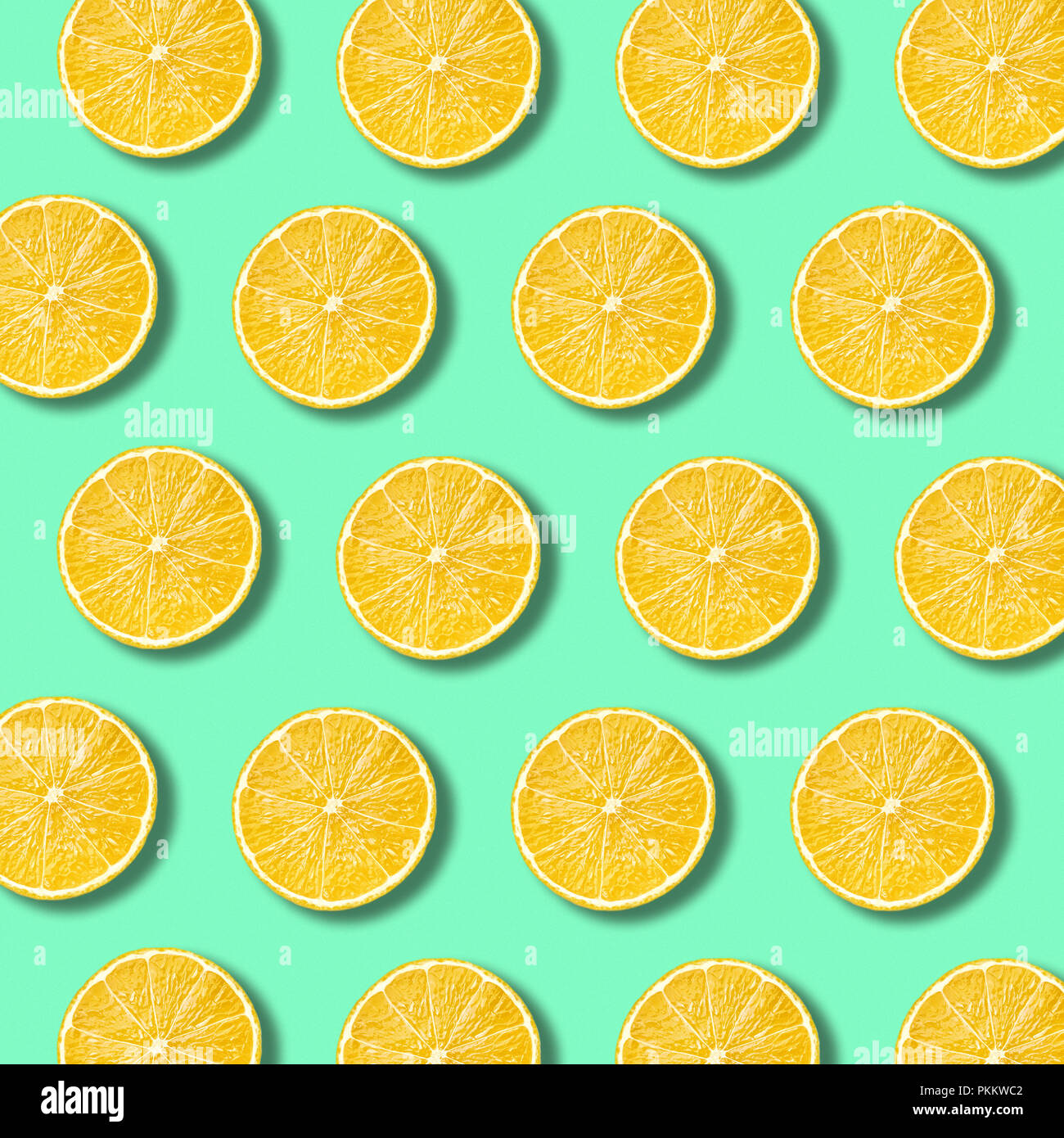 Lemon slices pattern on light vibrant green color background. Minimal flat lay food texture - Stock Image
