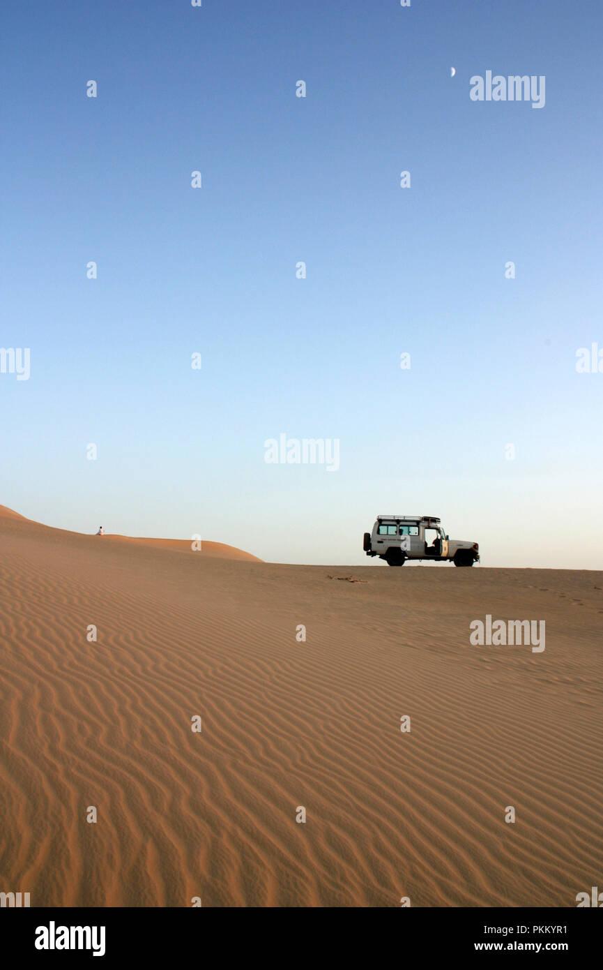 Egyptian Berber praying next to his off-road vehicle during a Sahara Desert Safari near Siwa Oasis, Egypt - Stock Image