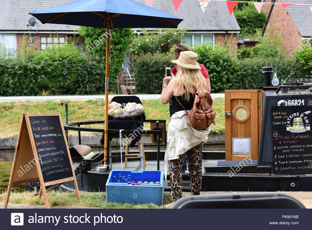 Blonde woman taking pictures of a floating cafe on the canal close to Llangollen, Wales. - Stock Image