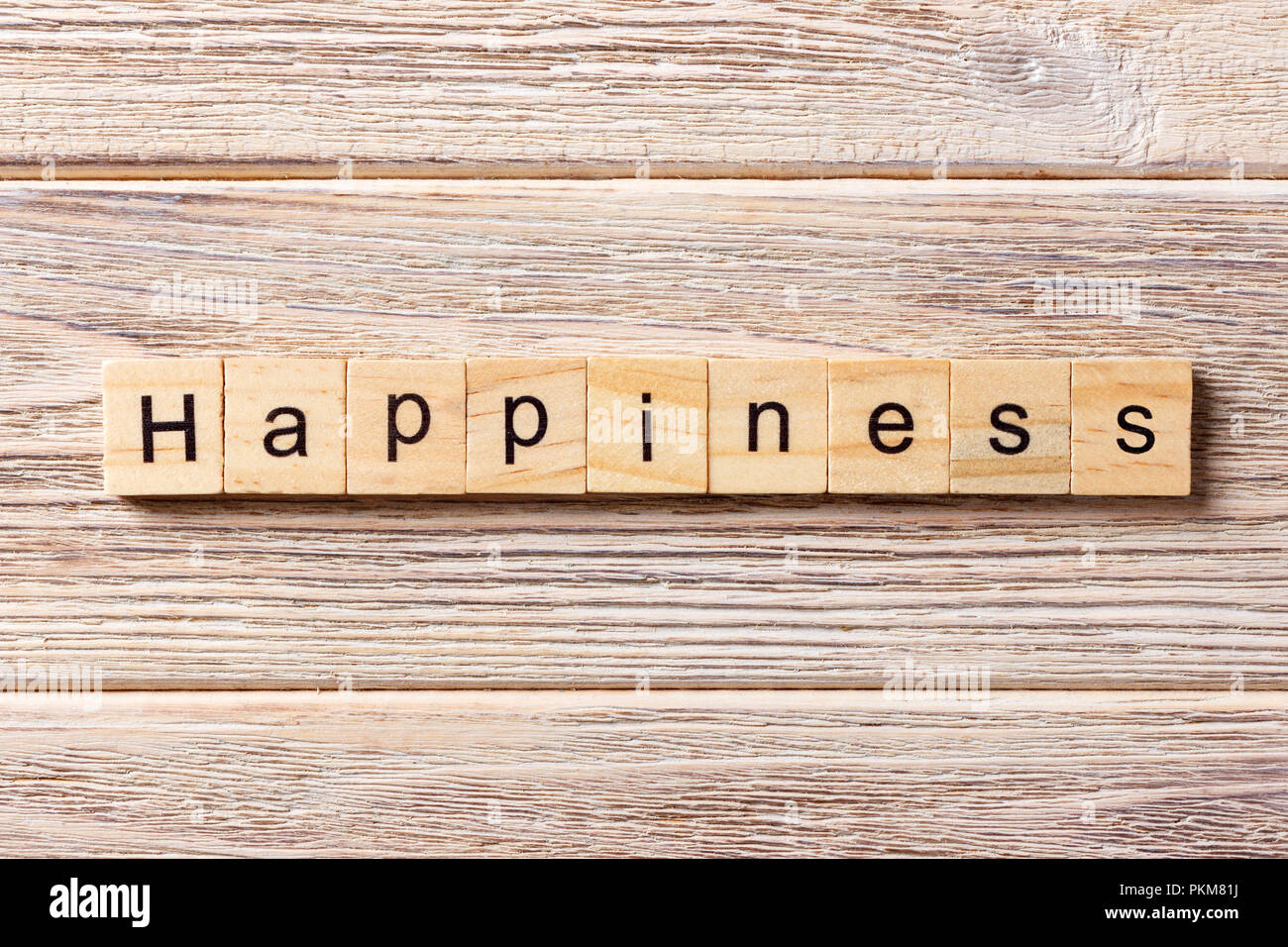 Happiness word written on wood block. Happiness text on table, concept. - Stock Image