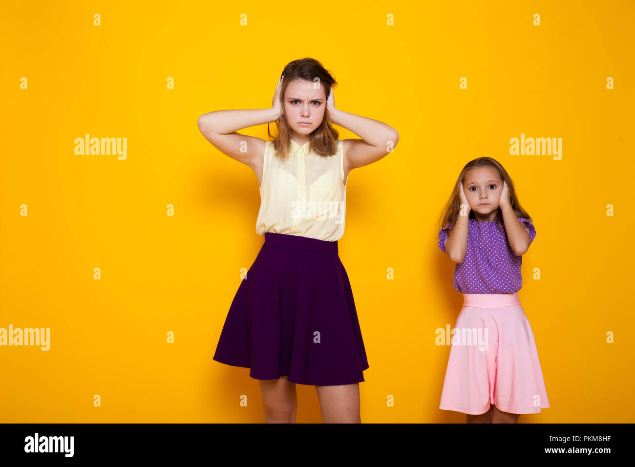 two girls close their ears from noise - Stock Image