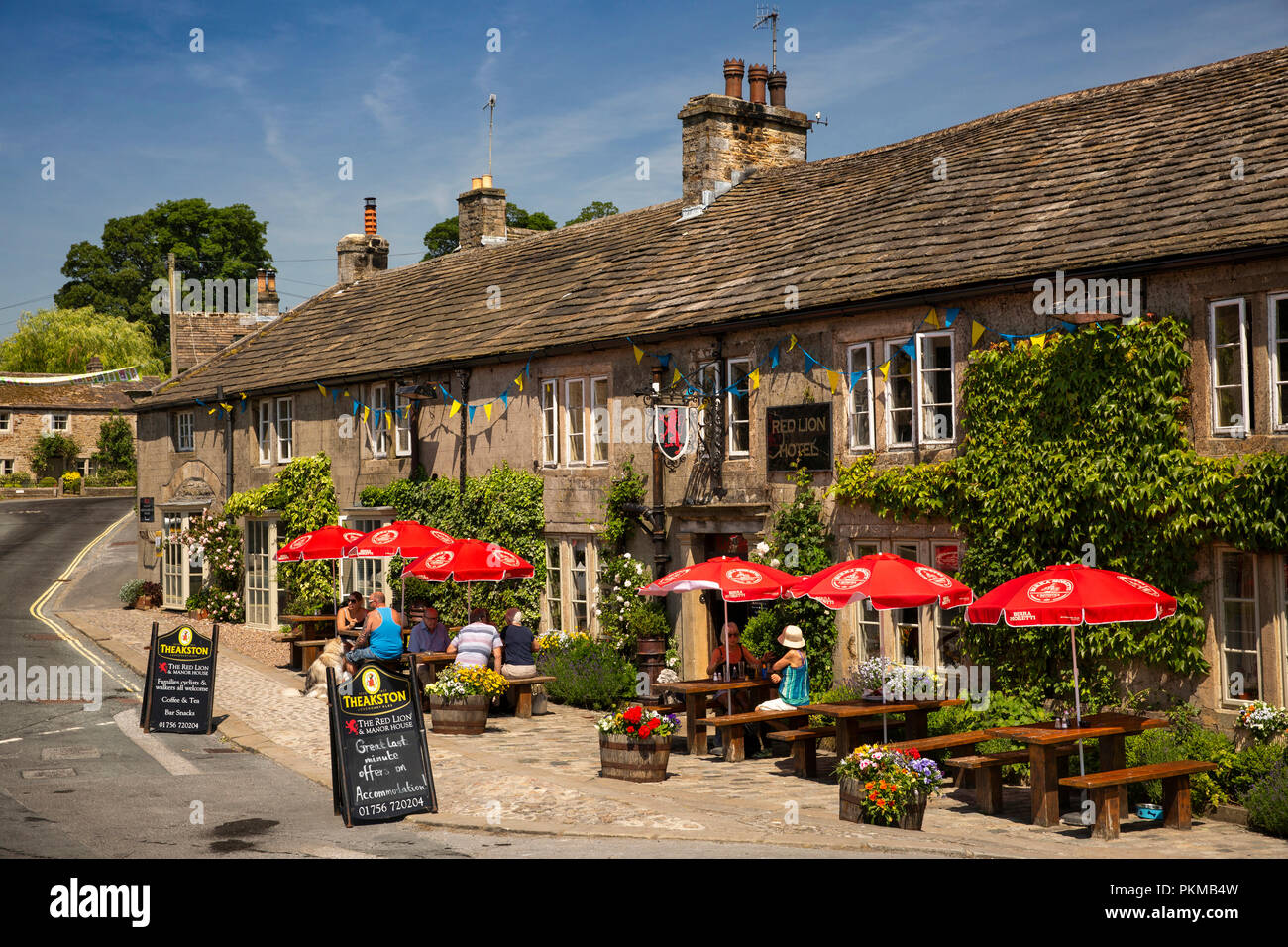 UK, Yorkshire, Wharfedale, Burnsall, Red Lion and Manor House hotel customers outside in sunshine Stock Photo
