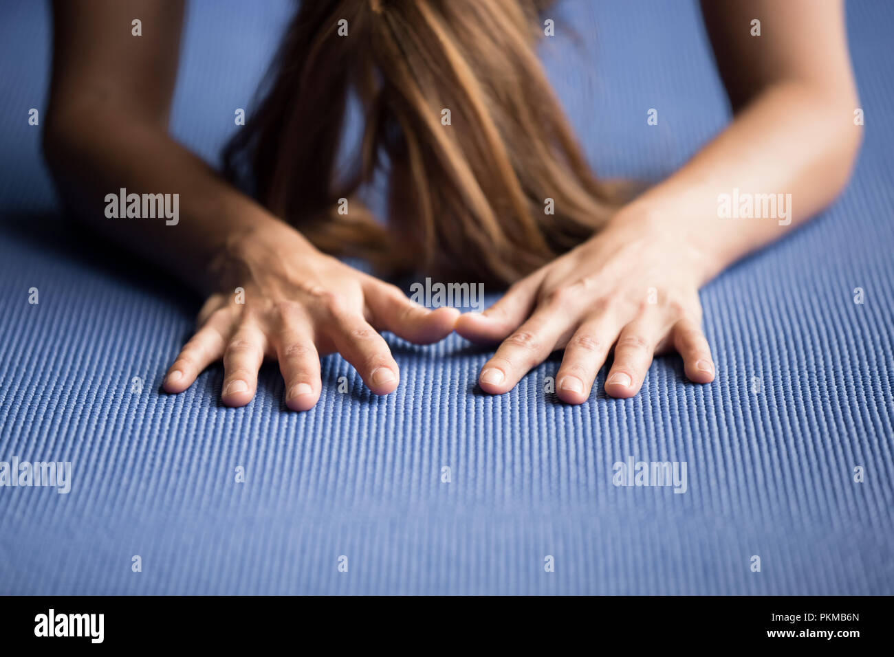 Sporty woman practicing yoga on a blue mat - Stock Image