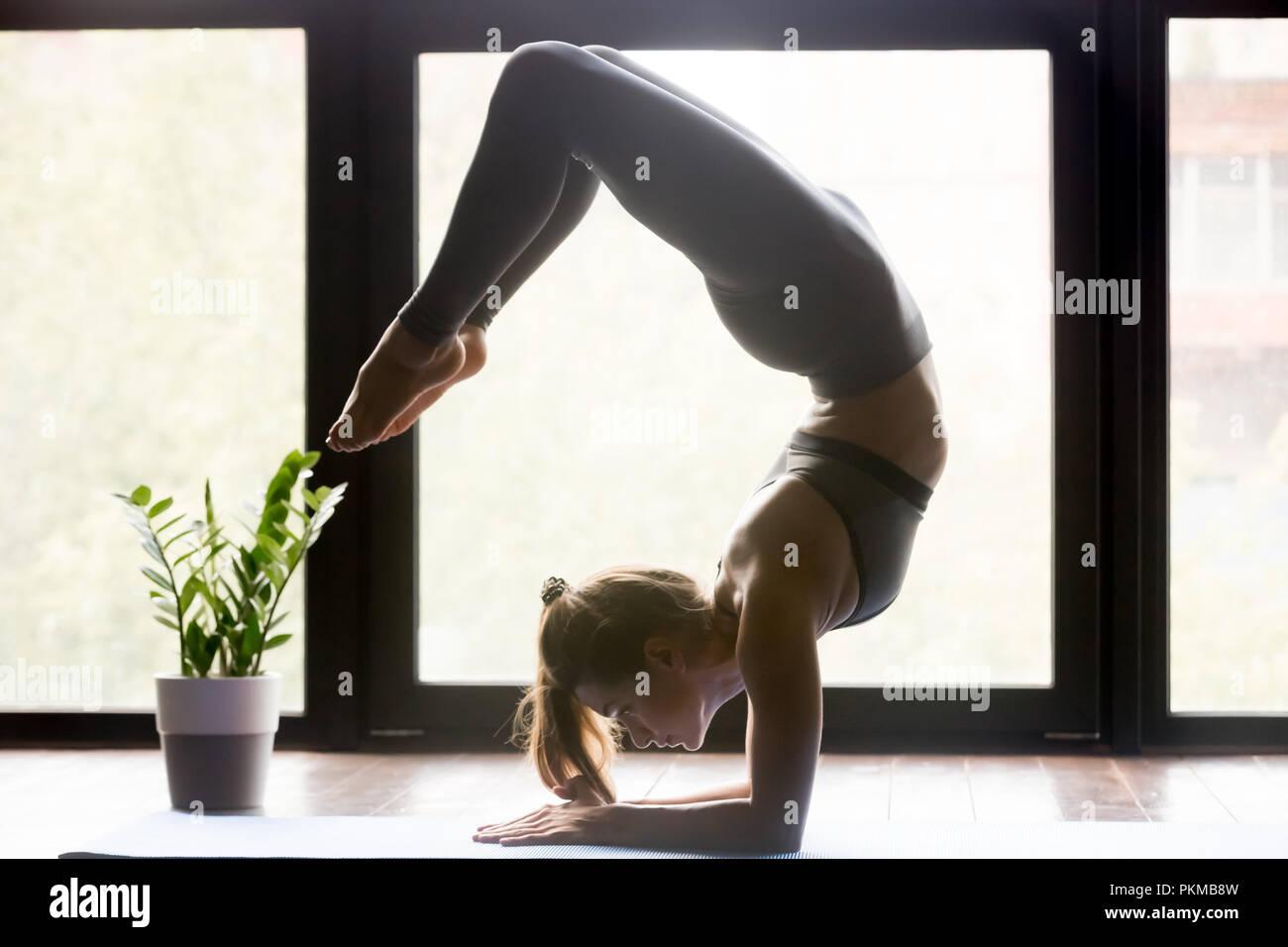 a98e2da45ccbf Young sporty woman doing yoga Scorpion backbend pose Stock Photo ...