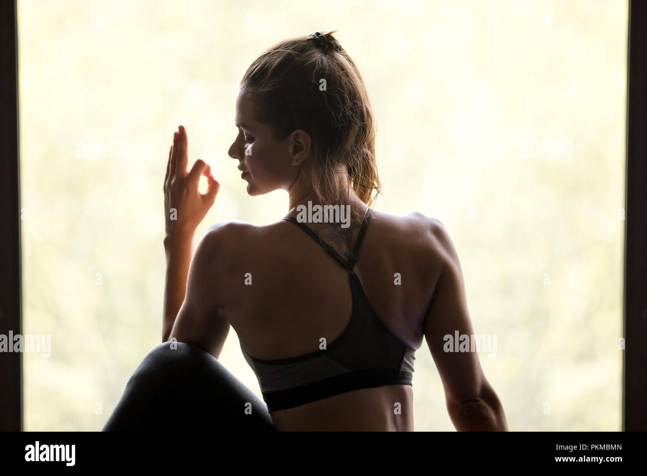 Young sporty woman in Ardha Matsyendrasana pose, close up - Stock Image