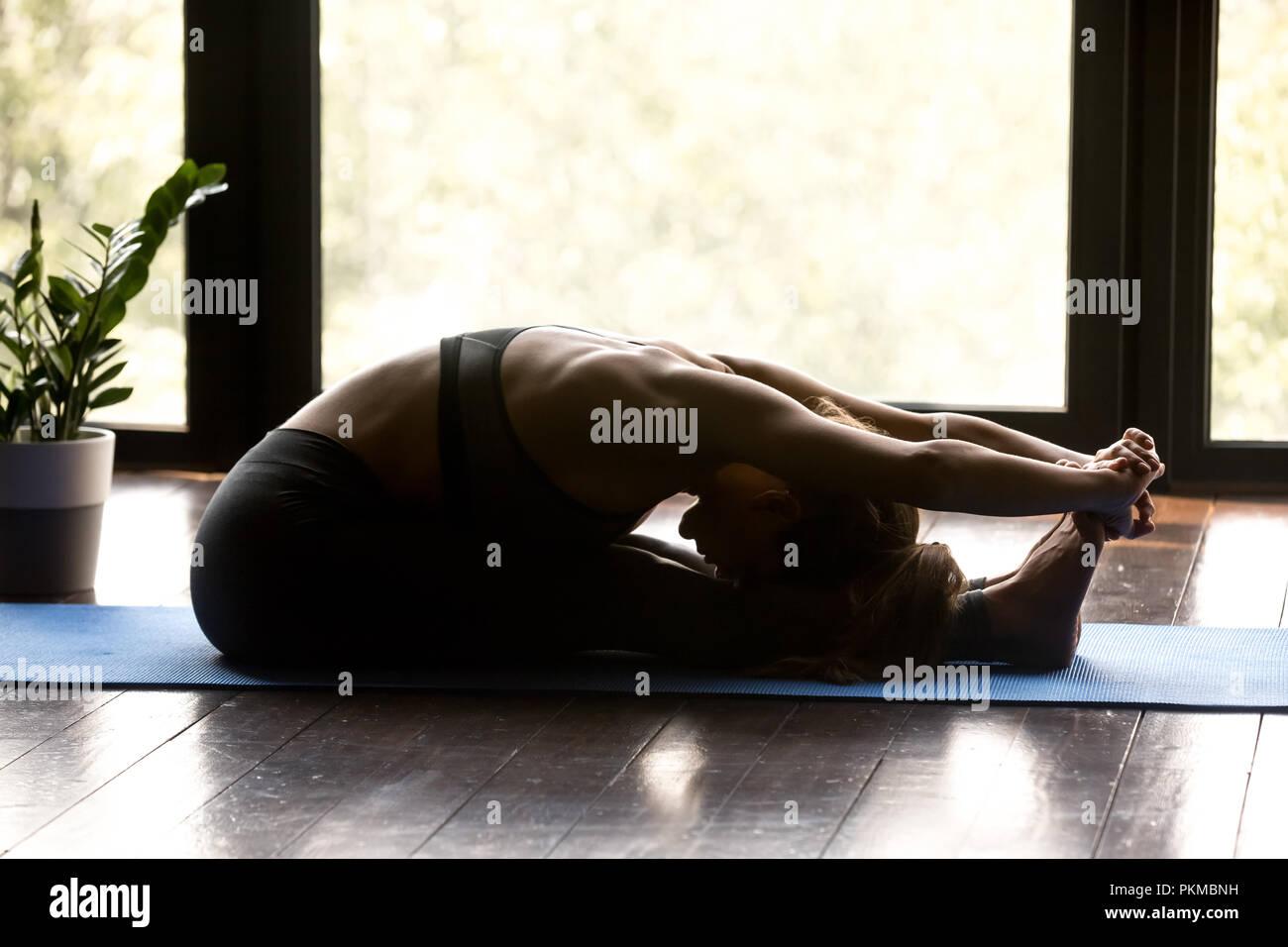 Young sporty woman doing paschimottanasana yoga exercise - Stock Image
