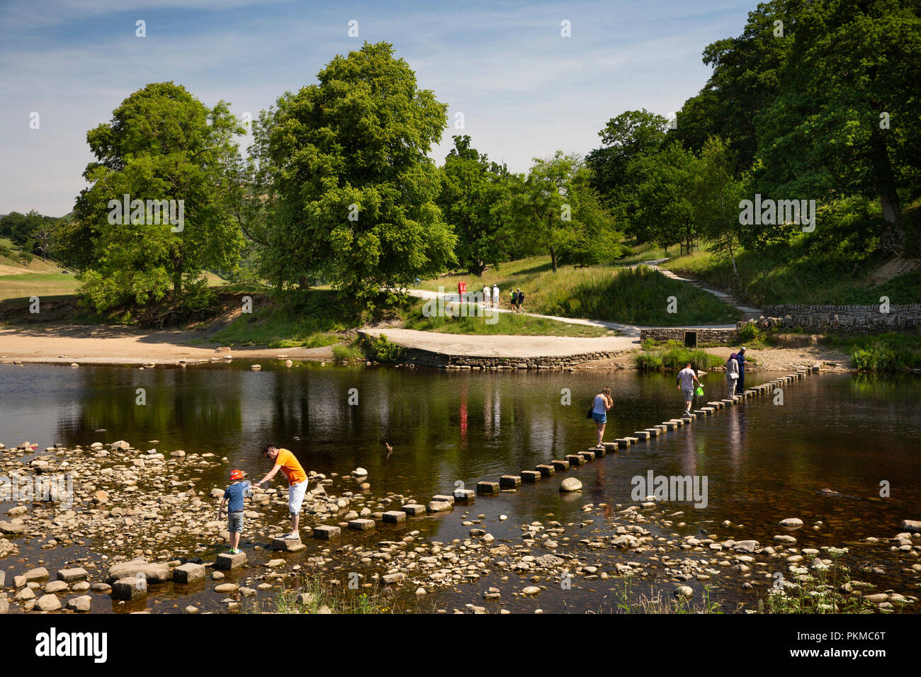 UK, Yorkshire, Wharfedale, Bolton Abbey, visitors crossing stepping stones over River Wharfe - Stock Image