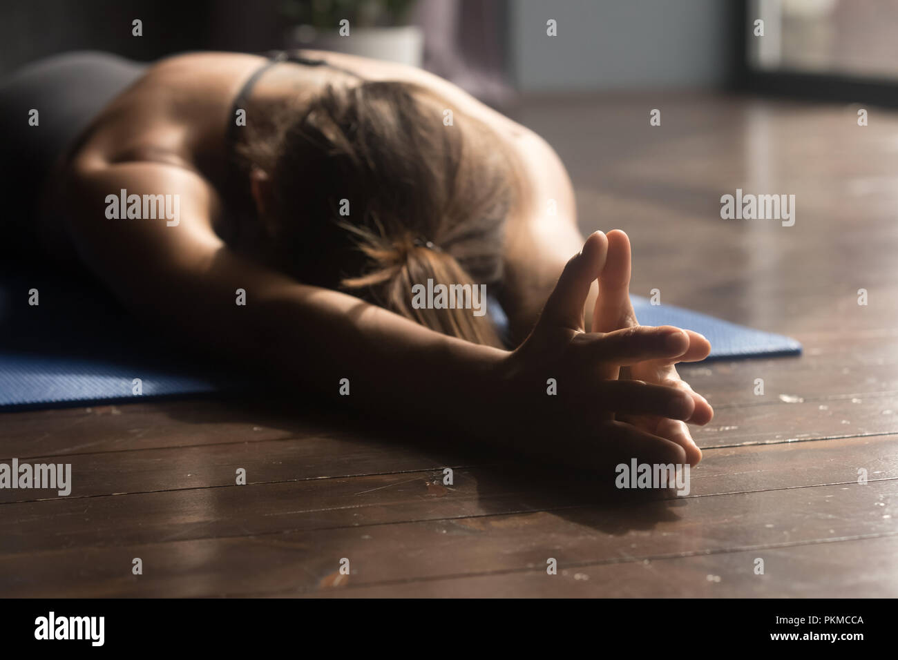 Young sporty woman doing breathing exercise lying on the floor - Stock Image