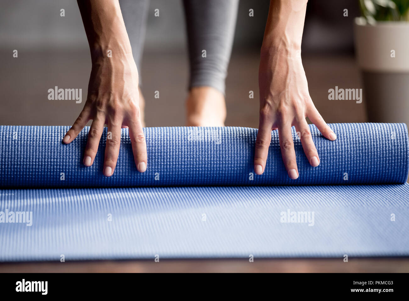 Girls hand folding blue exercise mat on the floor - Stock Image