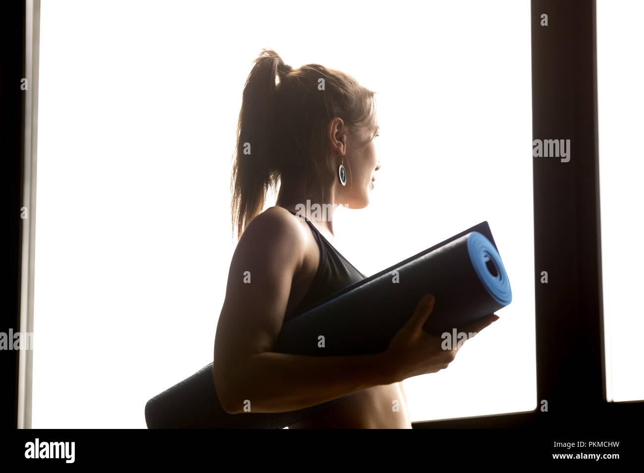 Sporty woman holding blue yoga mat, healthy lifestyle concept - Stock Image