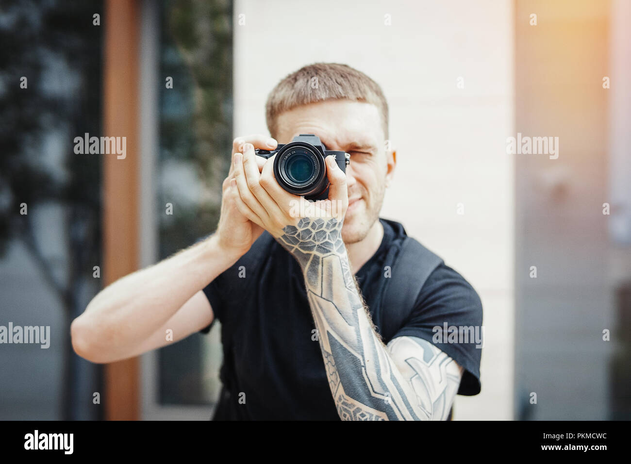 Close up of attractive man making photos at cityscape background - Stock Image