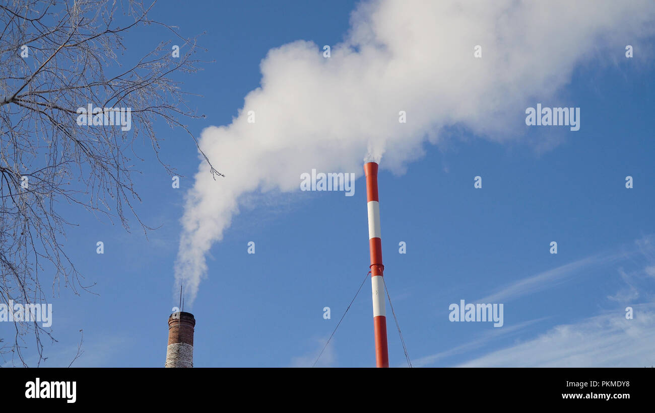Boiler room in the winter season, from the chimneys rise up clouds of steam. Pipes of a thermal power plant. Boiler house, pipe plant, boiler plant. - Stock Image