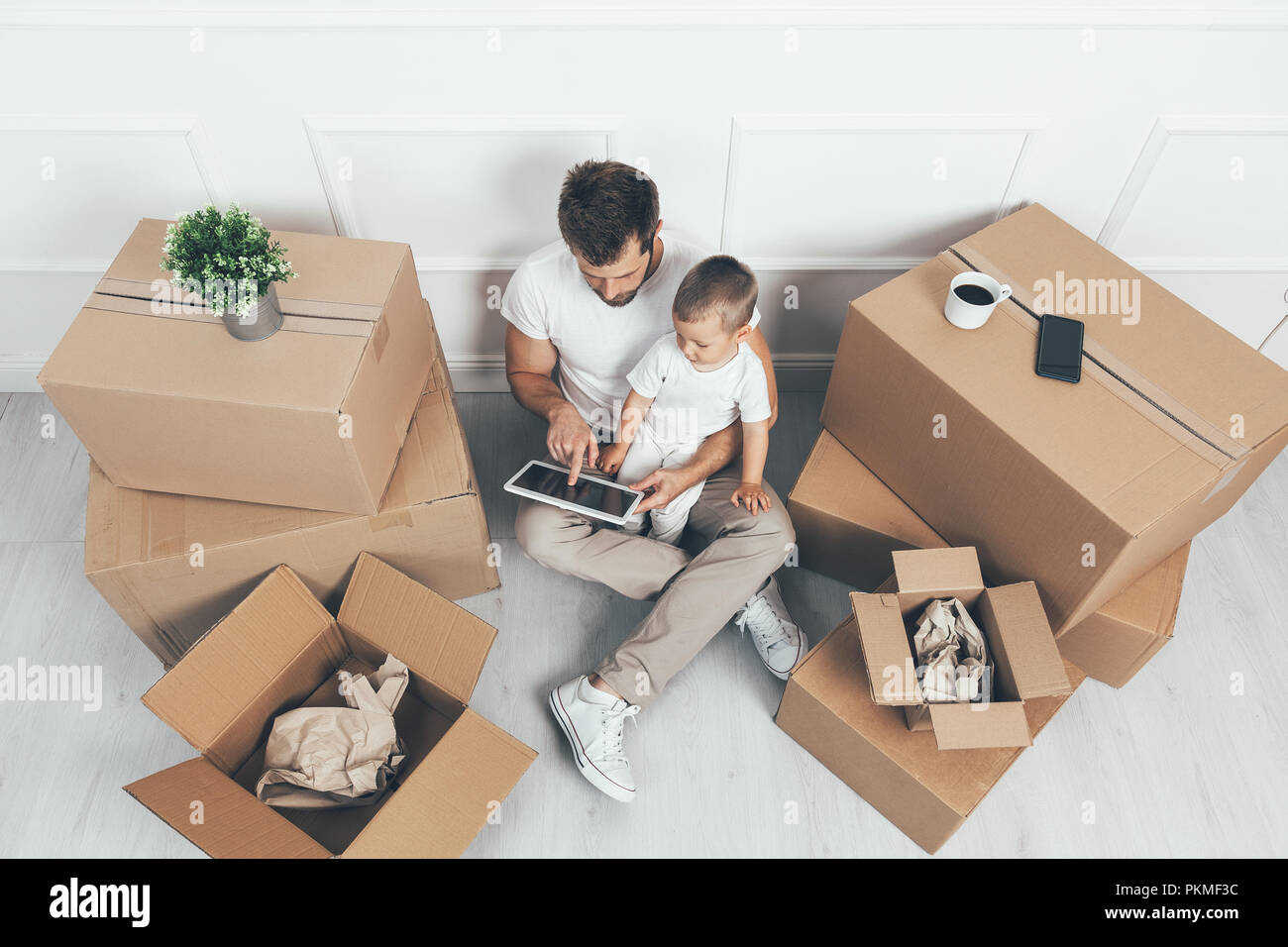Top view. Father and son moving into their new home - Stock Image