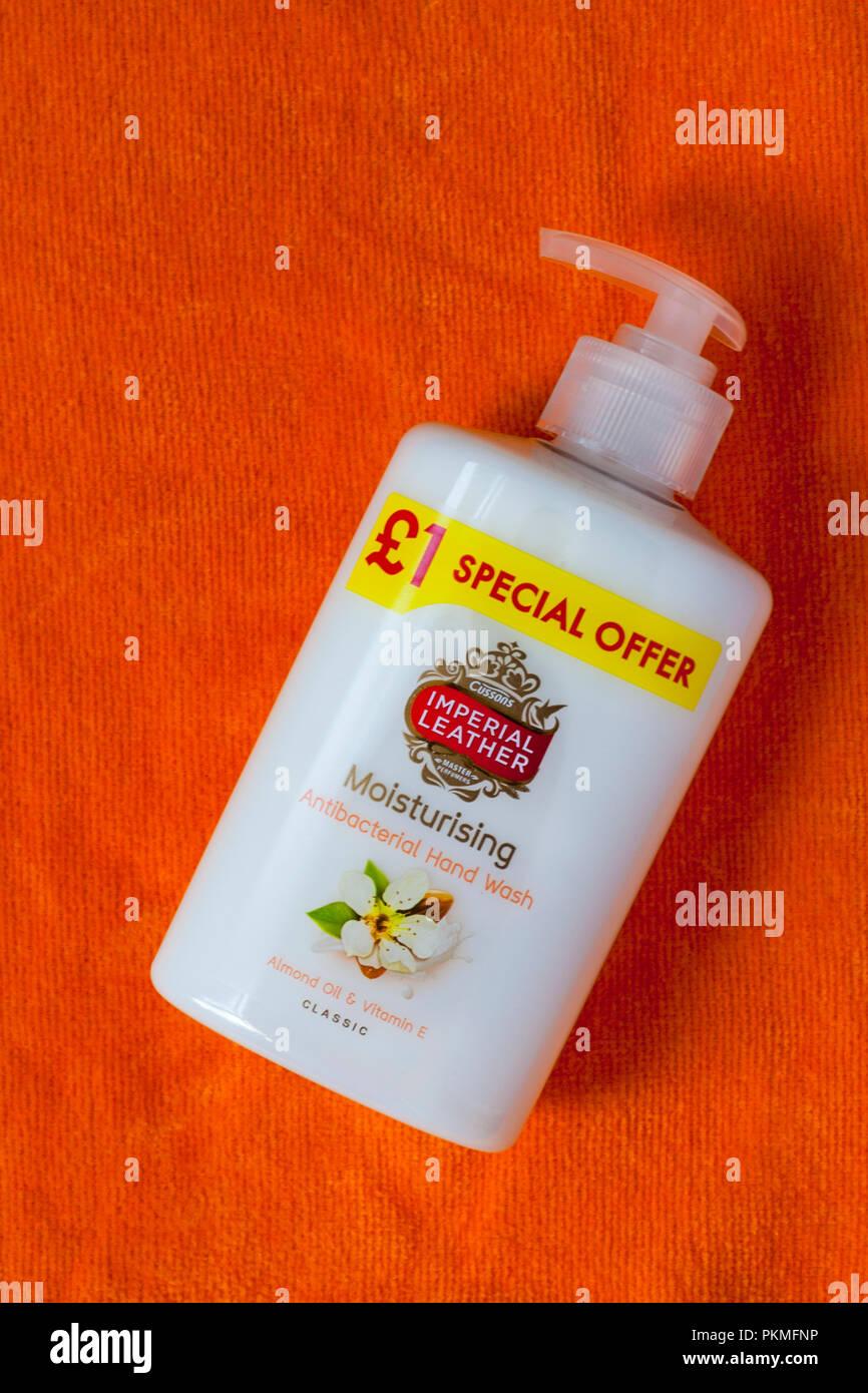 dispenser bottle of Imperial Leather moisturising antibacterial hand wash  - Almond Oil & Vitamin E classic on orange coloured towel - Stock Image