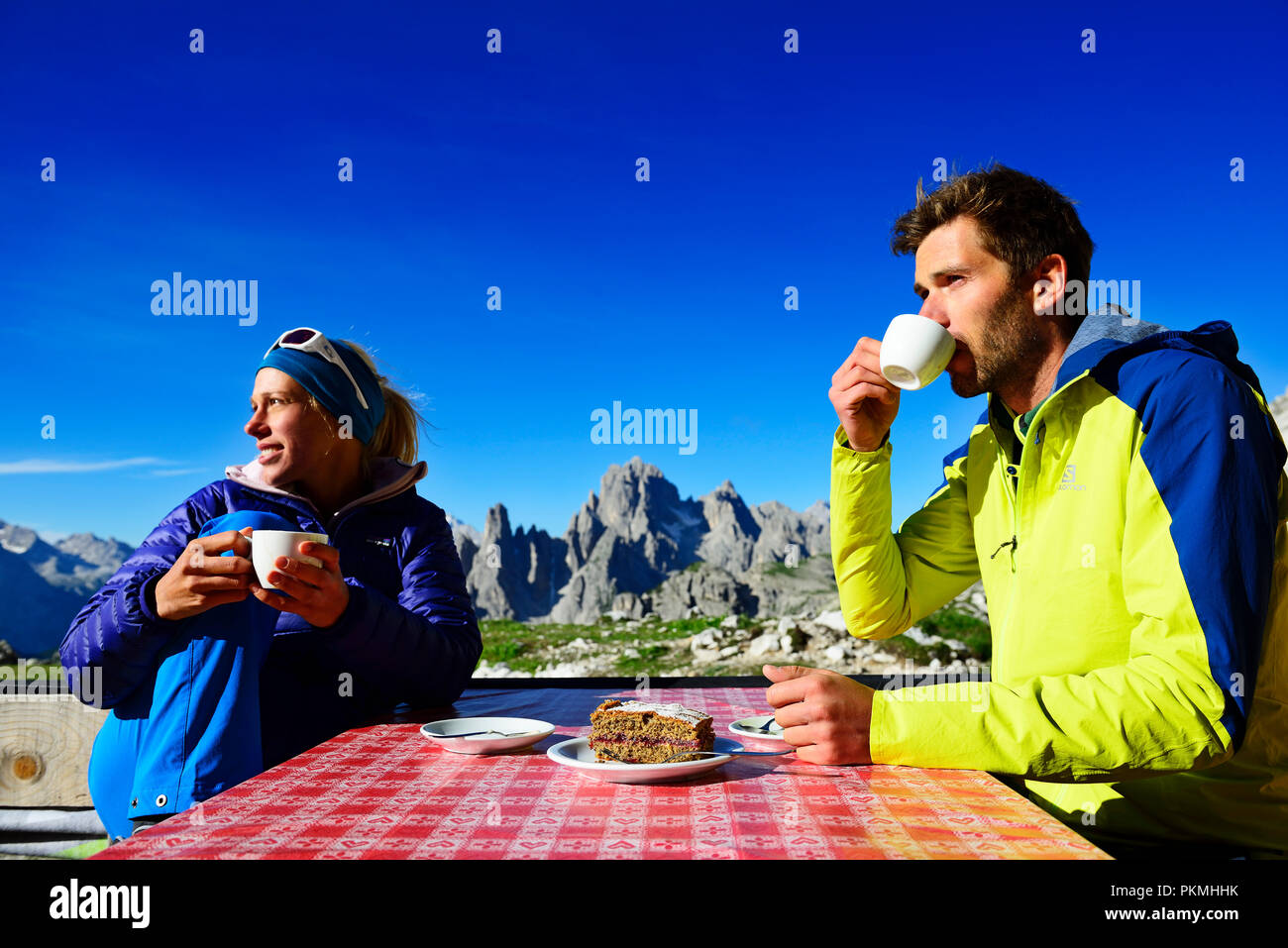 Hikers on the south side of the Three Peaks pause in front of the Lavaredo Hut, Sexten Dolomites, Alta Pusteria, South Tyrol - Stock Image