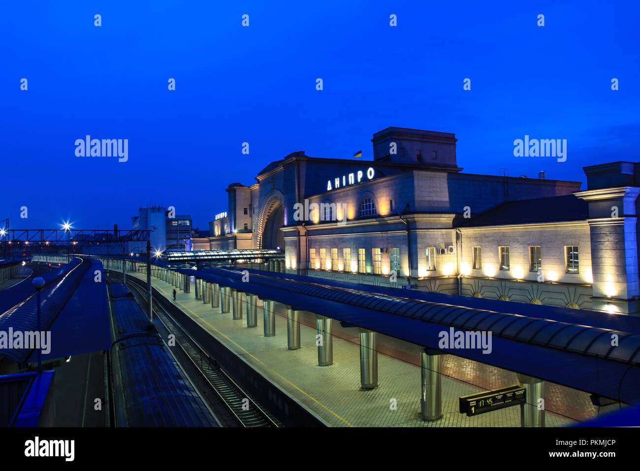 The platform and the building of the railway station with the inscription `Dnipro` in Dnipropetrovsk city at night. Dnepr, Dnepropetrovsk, Ukraine - Stock Image