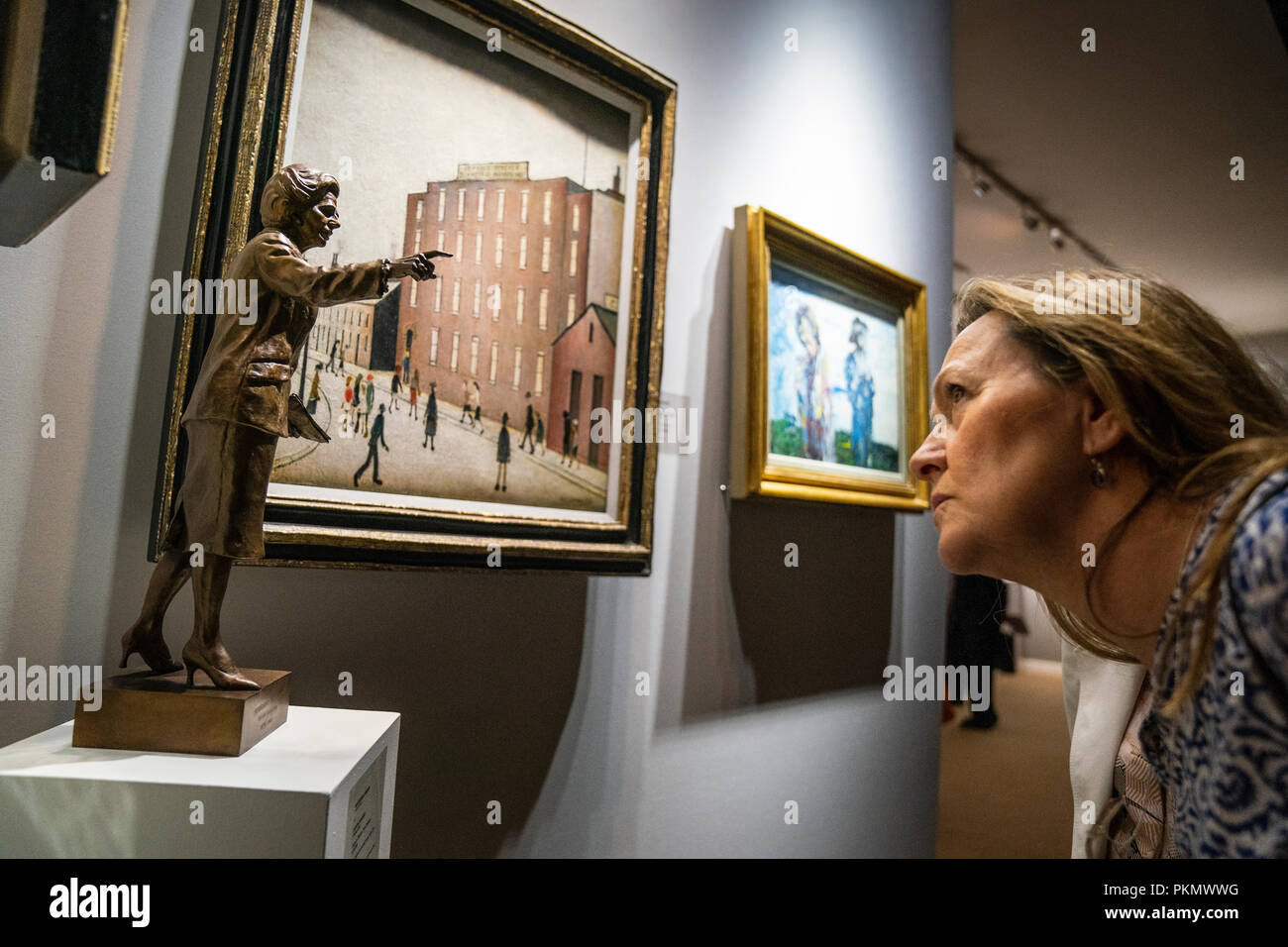 LONDON - SEPTEMBER 14: Visitors look at a bronze figure of Margaret Thatcher, next to a painting by LS Lowry, at the annual LAPADA Art and Antiques Fair opened today, September 14, 2018,  in Berkeley Square, London. Over 100 exhibitors present work from across the art, antiques, design and decorative arts spectrum. The Fair runs from September 14-19, 2018. Photo by David Levenson/Alamy Live news - Stock Image