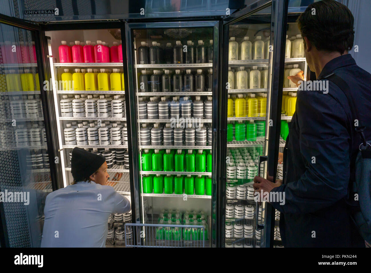 New York, USA. 14th September 2018. A worker stocks the shelves as a customer makes his choice in the Dirty Lemon beverage store in New York on Friday, September 14, 2018. The store called 'The Drug Store' in the Tribeca neighborhood operates on the honor system where after you make your choice you text the company and they charge your pre-set up account.  All the beverages are based on lemon-flavored water with collagen, rose water, magnesium or other ingredients added to the various flavors in the better- Credit: Richard Levine/Alamy Live News - Stock Image