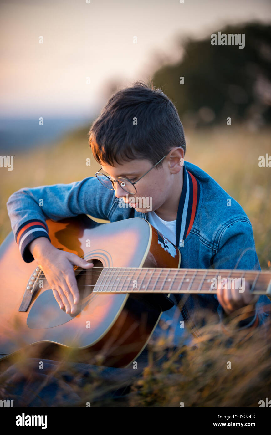A little boy with glasses sitting in the field and enthusiastically playing the guitar. Nature, beauty. Stock Photo