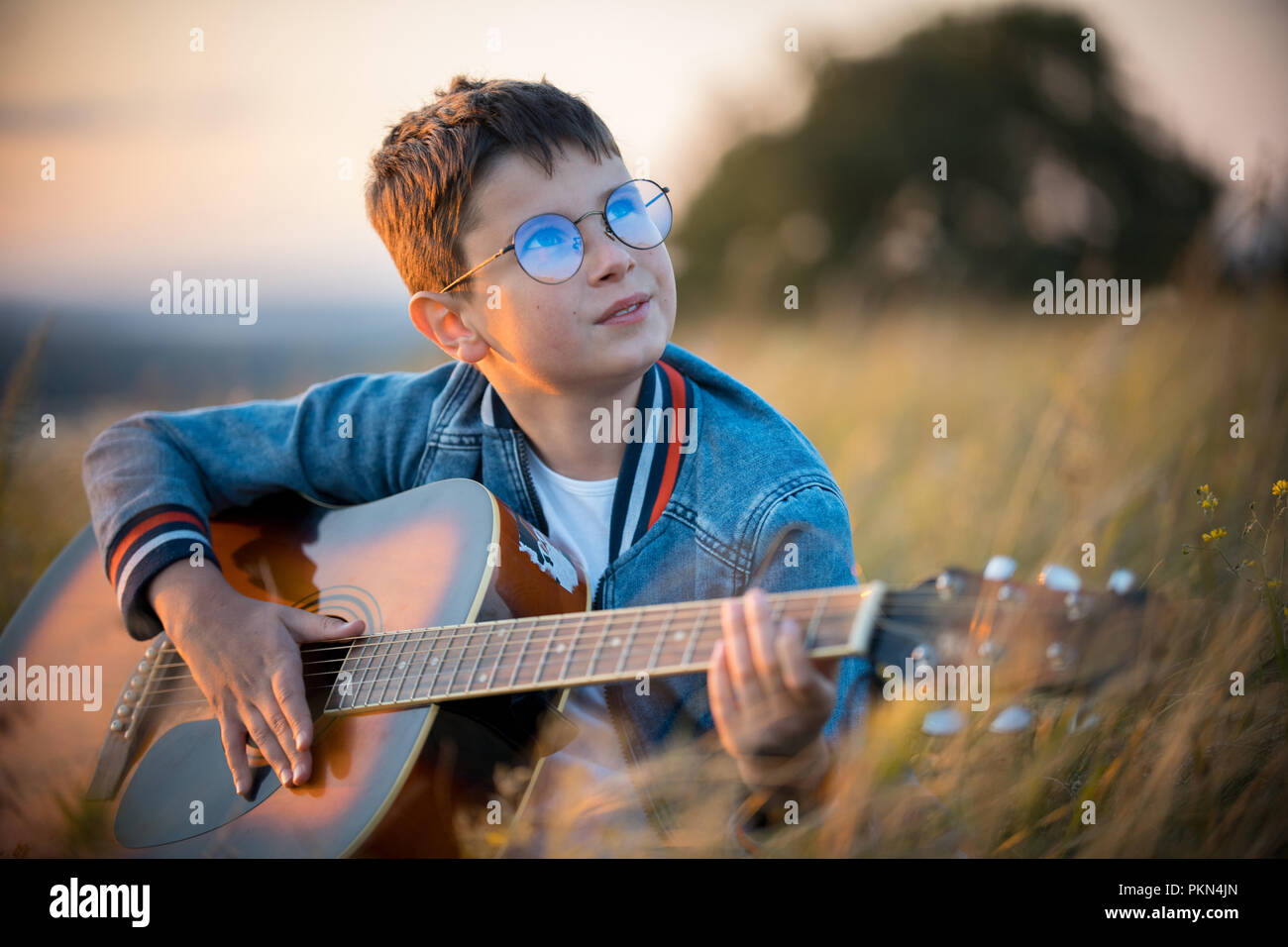 A little boy with glasses playing guitar in the field. Nature, beauty. Stock Photo