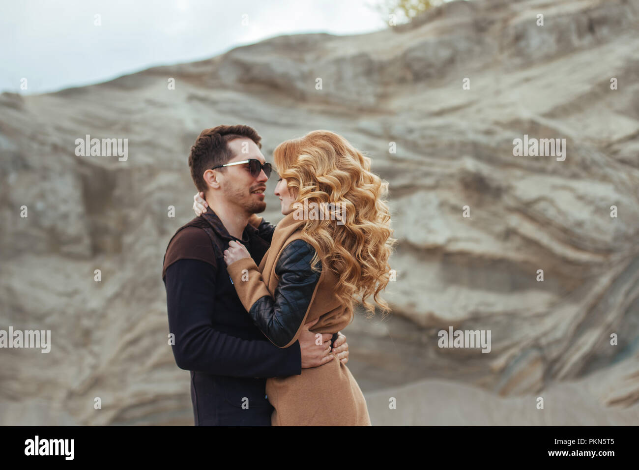 Beautiful couple in love on Valentine's Day. Happy young couple walking on the sandy mountains on a cloudy day - Stock Image
