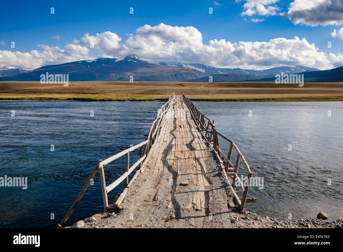 Shabby wooden bridge over a river with distant mountain range in background, Altai Mountains, Western Mongolia - Stock Image