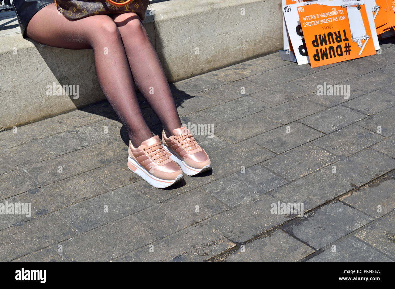 Girl wearing copper training shoes and tights during an anti_trump rally, London, England, UK. 2018 - Stock Image