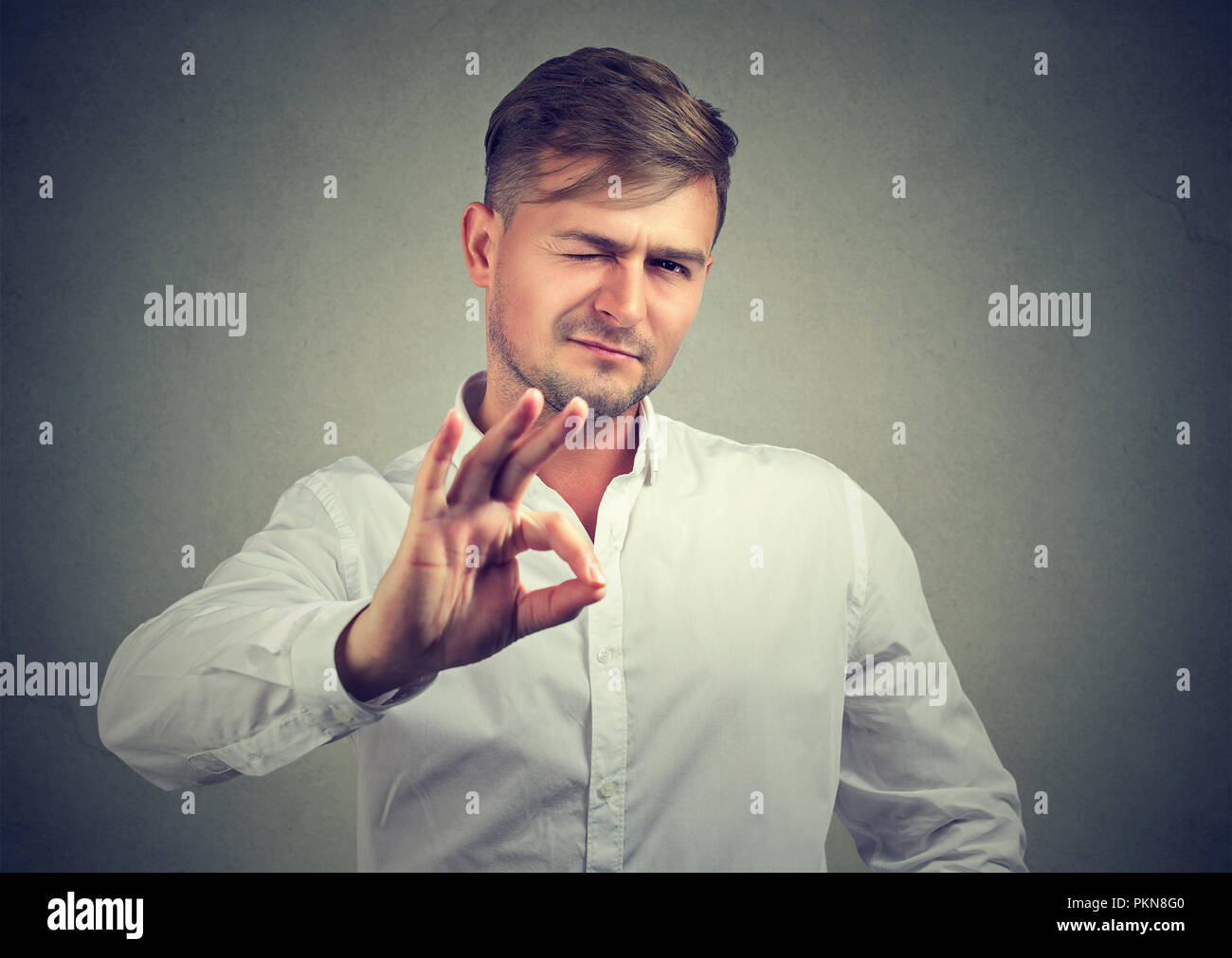 Handsome casual man winking at camera and showing OK gesture on gray background - Stock Image