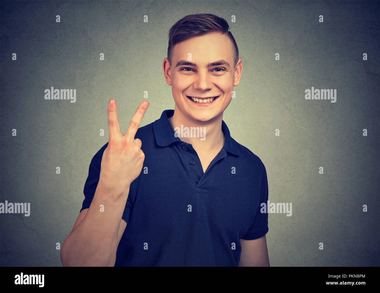 Young casual man smiling brightly and showing v sign while looking at camera on gray background - Stock Image